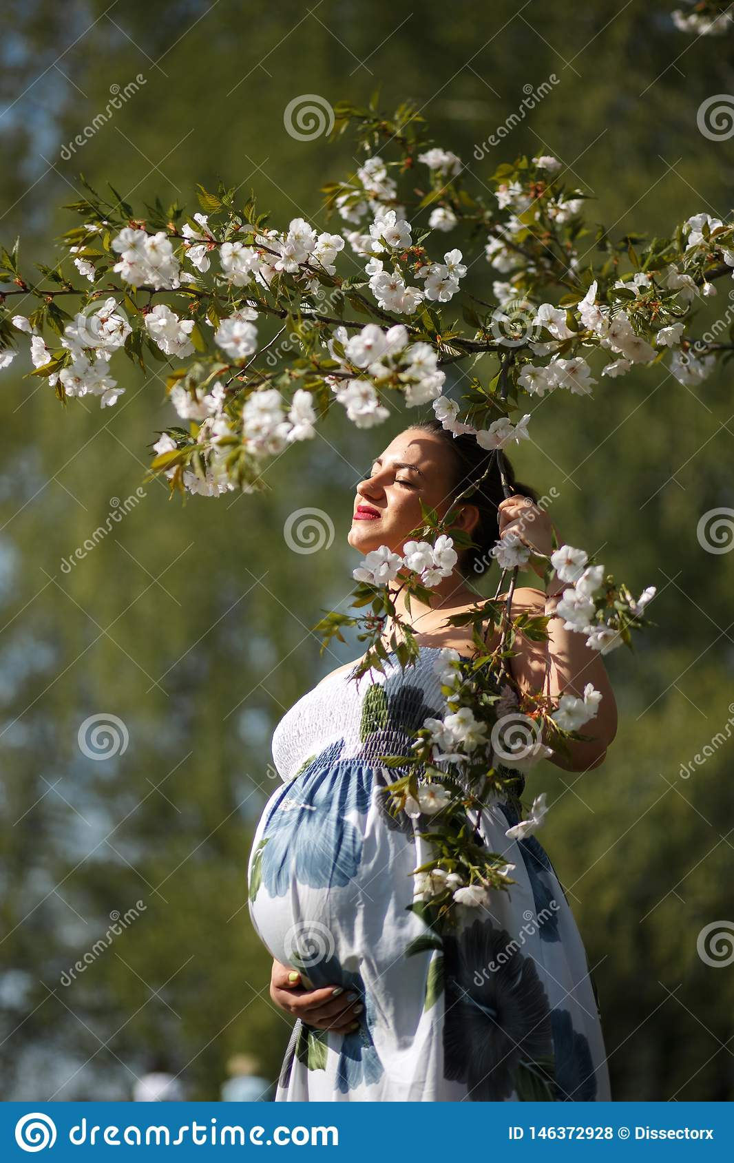 Happy young soon to be mother mom - Young traveler pregnant woman enjoys her leisure free time in a park with blossoming