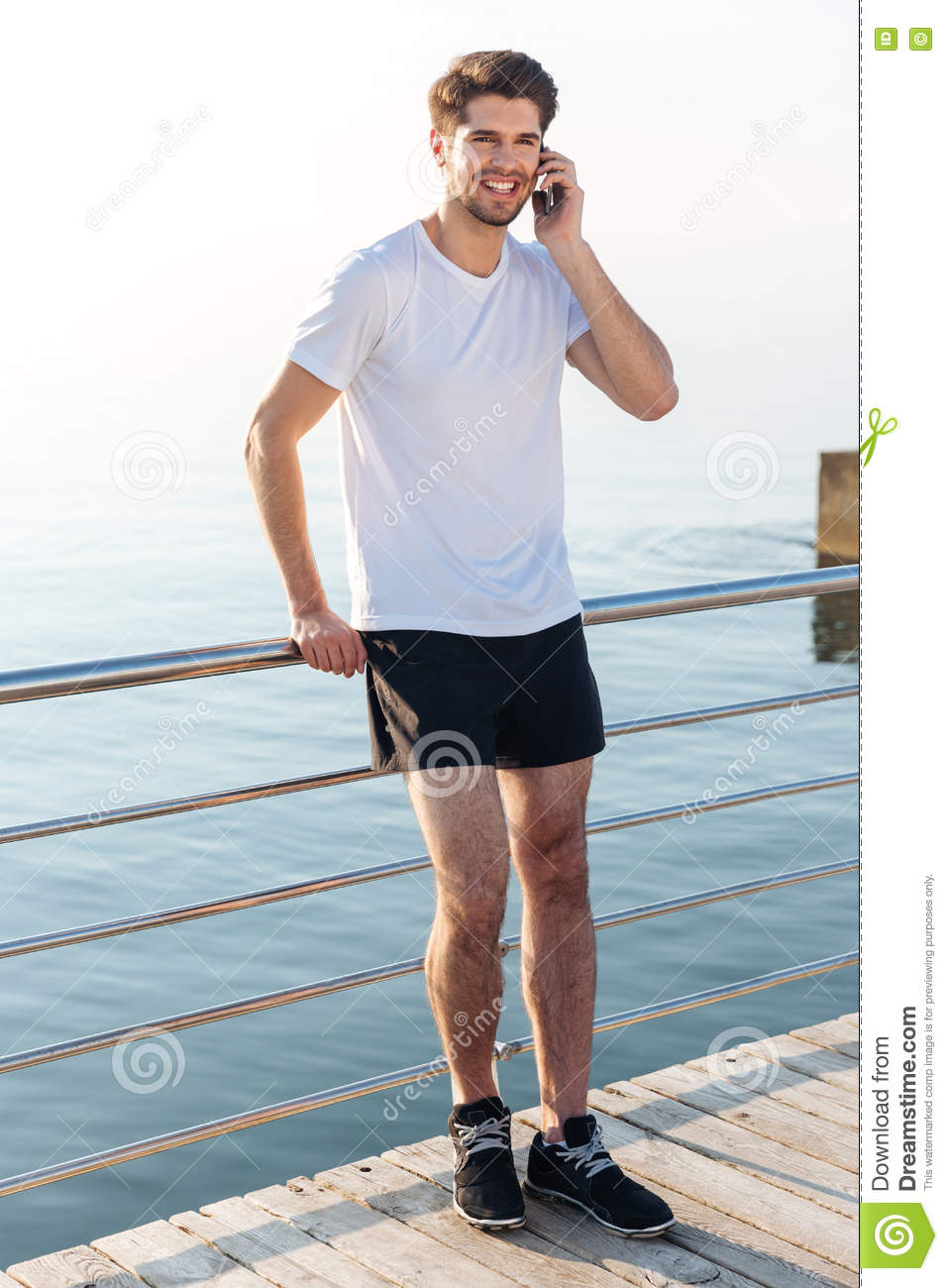 Happy young sportsman standing and talking on mobile phone