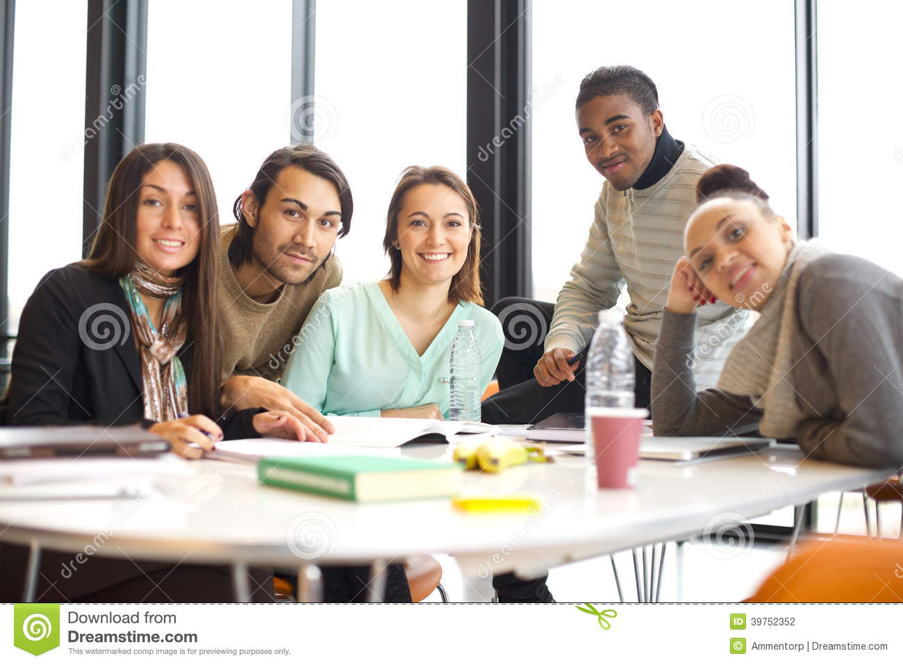 Portrait of a group of positive university students sitting at table
