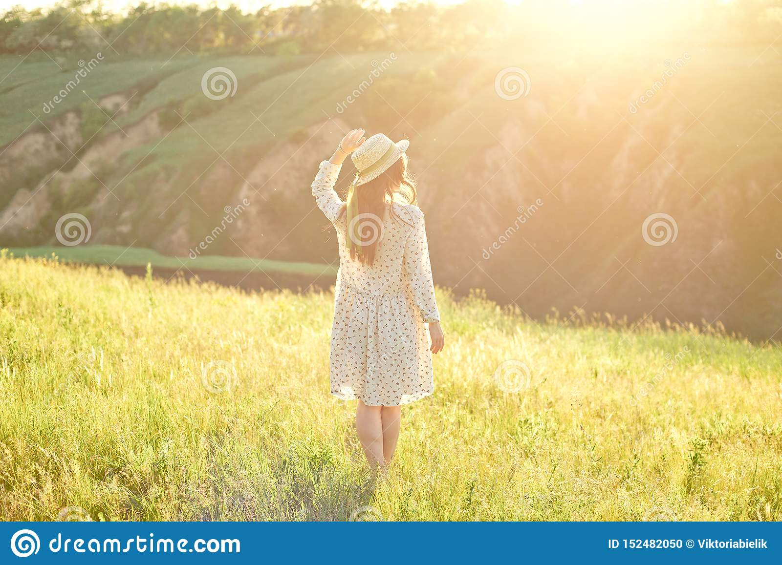Happy young teenage student girl wearing a summer dress and straw hat in hands. Walking outdoors at the park.