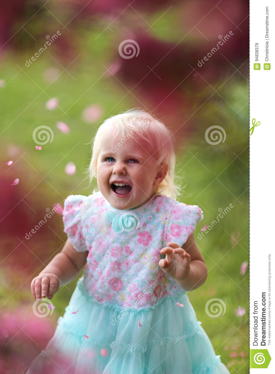 Happy Young Toddler Girl Laughing as Flower Petals Fall Off a Cr