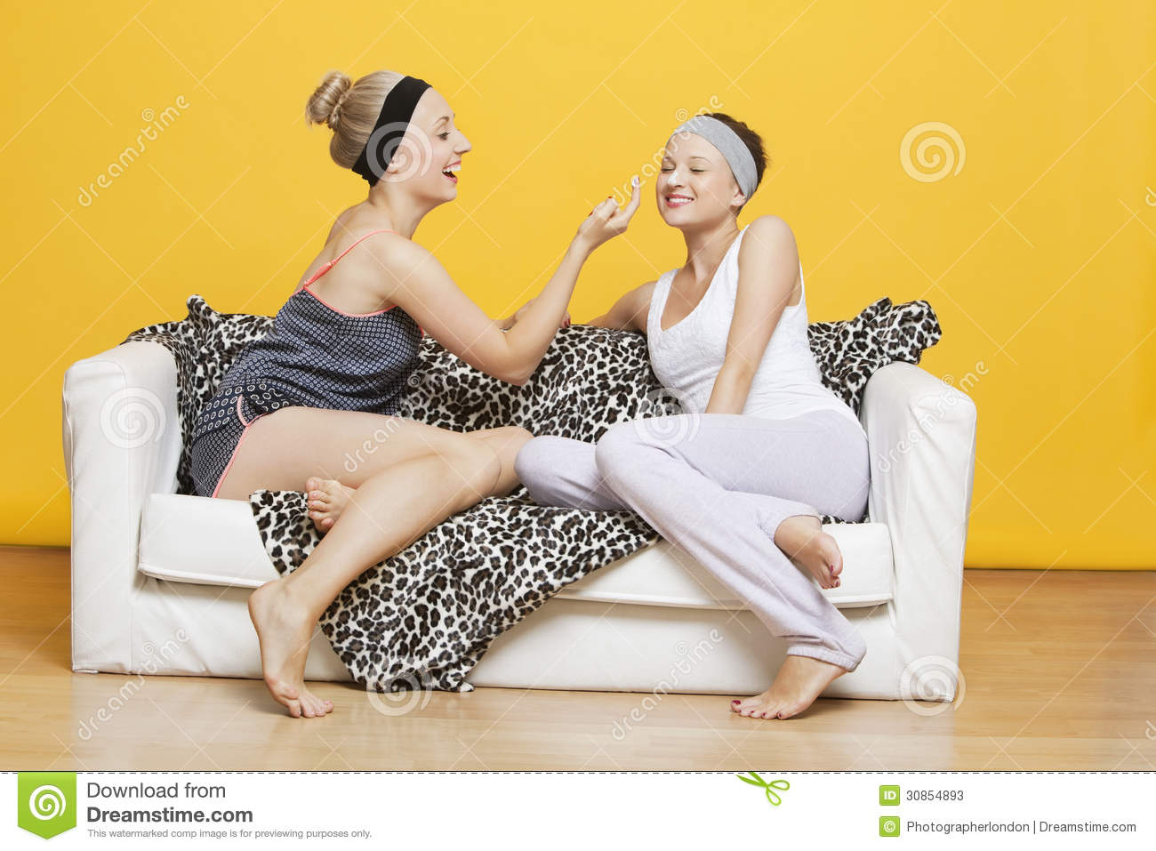 Happy Young Woman Applying Face Pack On Friend's Face While ...