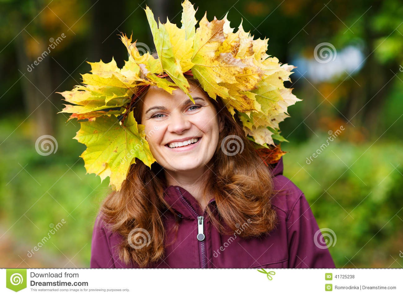 Happy young woman with autumn maple leaves garland in park.