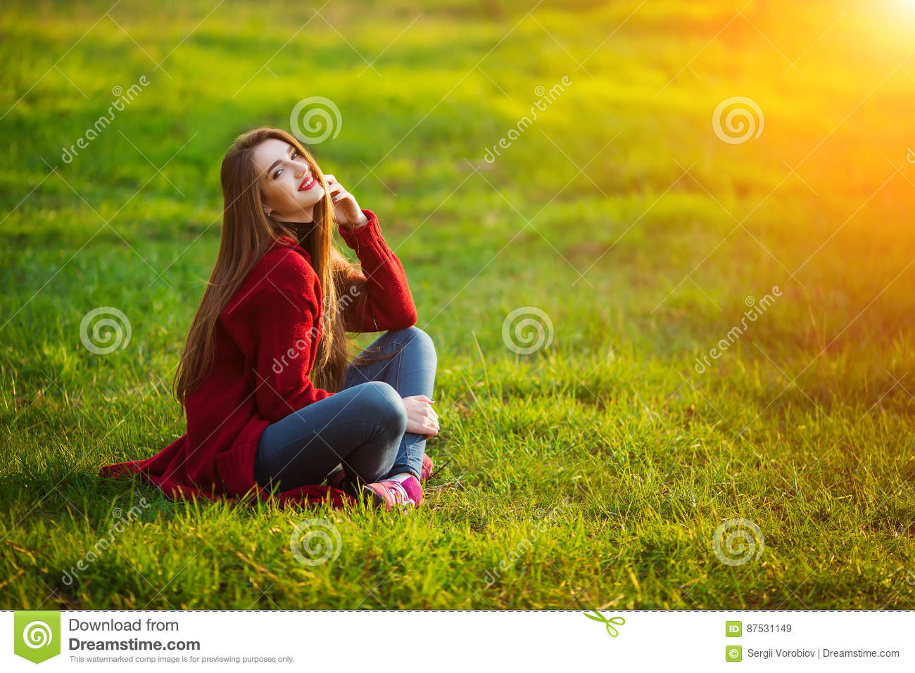 Happy young woman. Beautiful female with long healthy hair enjoying sun light in park sitting on green grass. Spring