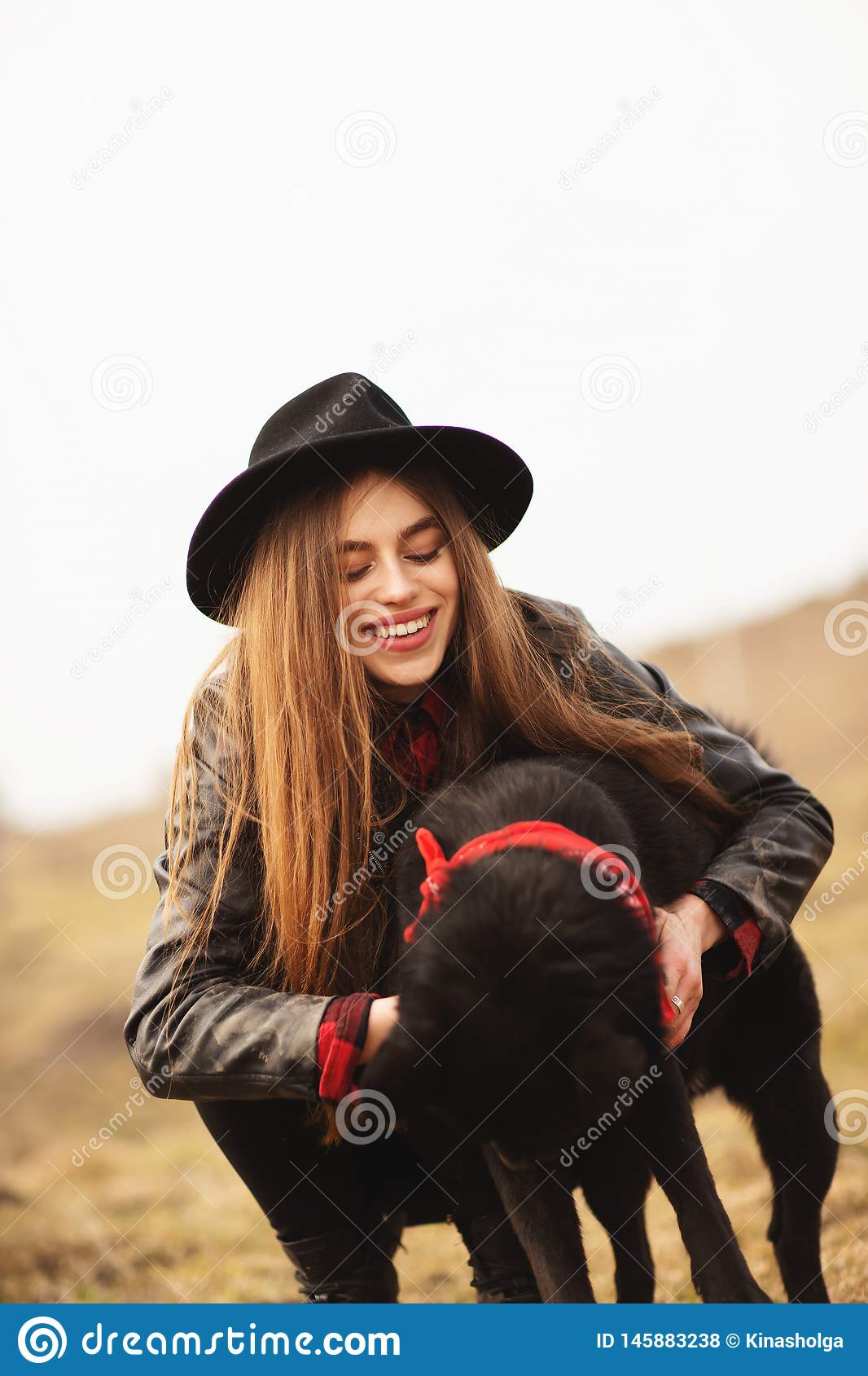 Happy young woman with black hat, plaing with her black dog on the shore of the lake