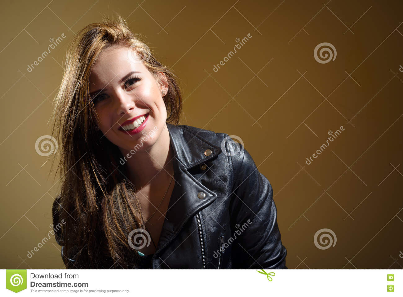 Happy young woman in black leather jacket on brown background