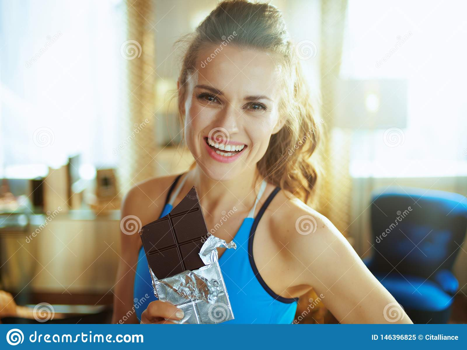 Happy young woman with chocolate bar in modern living room