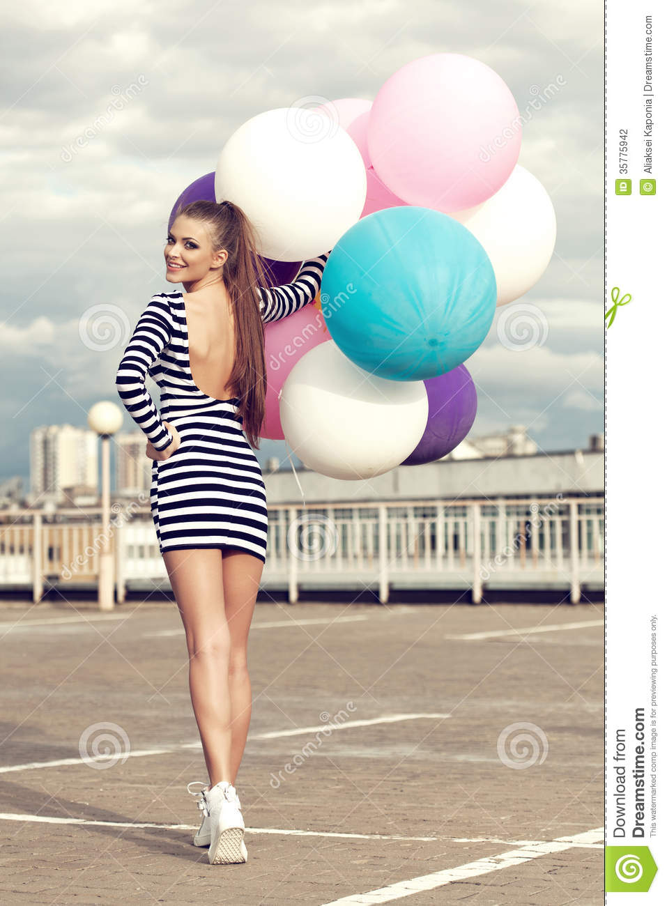 Happy young woman with big colorful latex balloons girl going back to the camera and turning outdoors lifestyle