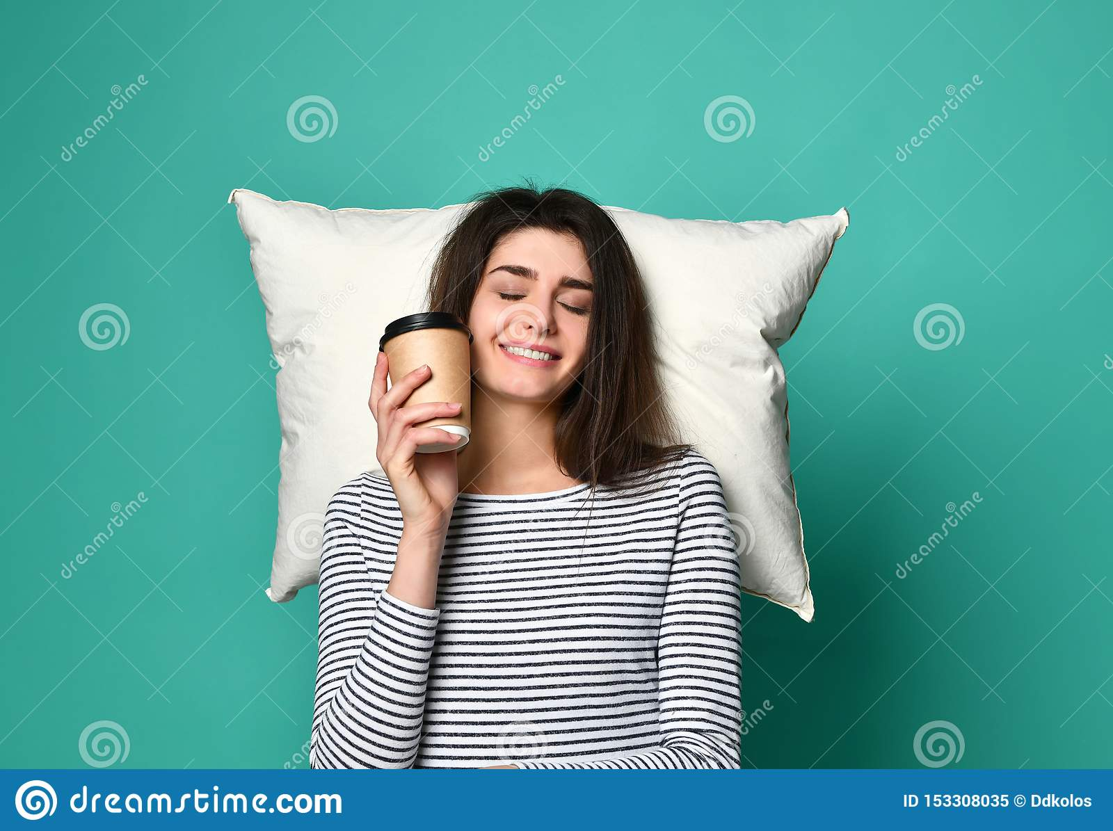 Happy young woman with a cup of coffee or tea in her hands, dreams on a pillow about anything