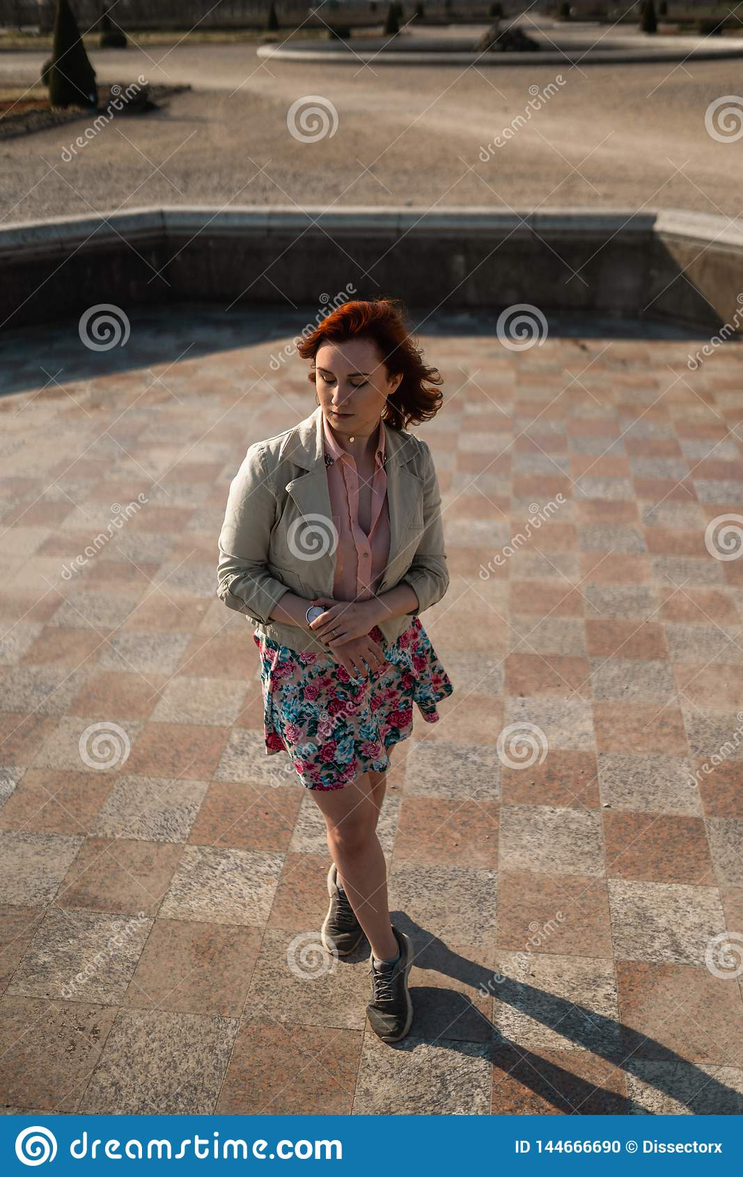 Happy young woman dancing in an empty fountain wearing a colorful skirt