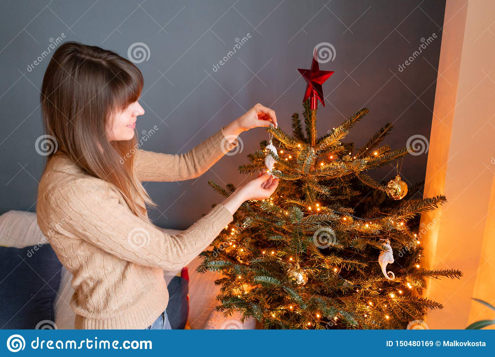 Happy young woman decorating christmas tree at home. Winter holidays in a house interior. Golden and white Christmas