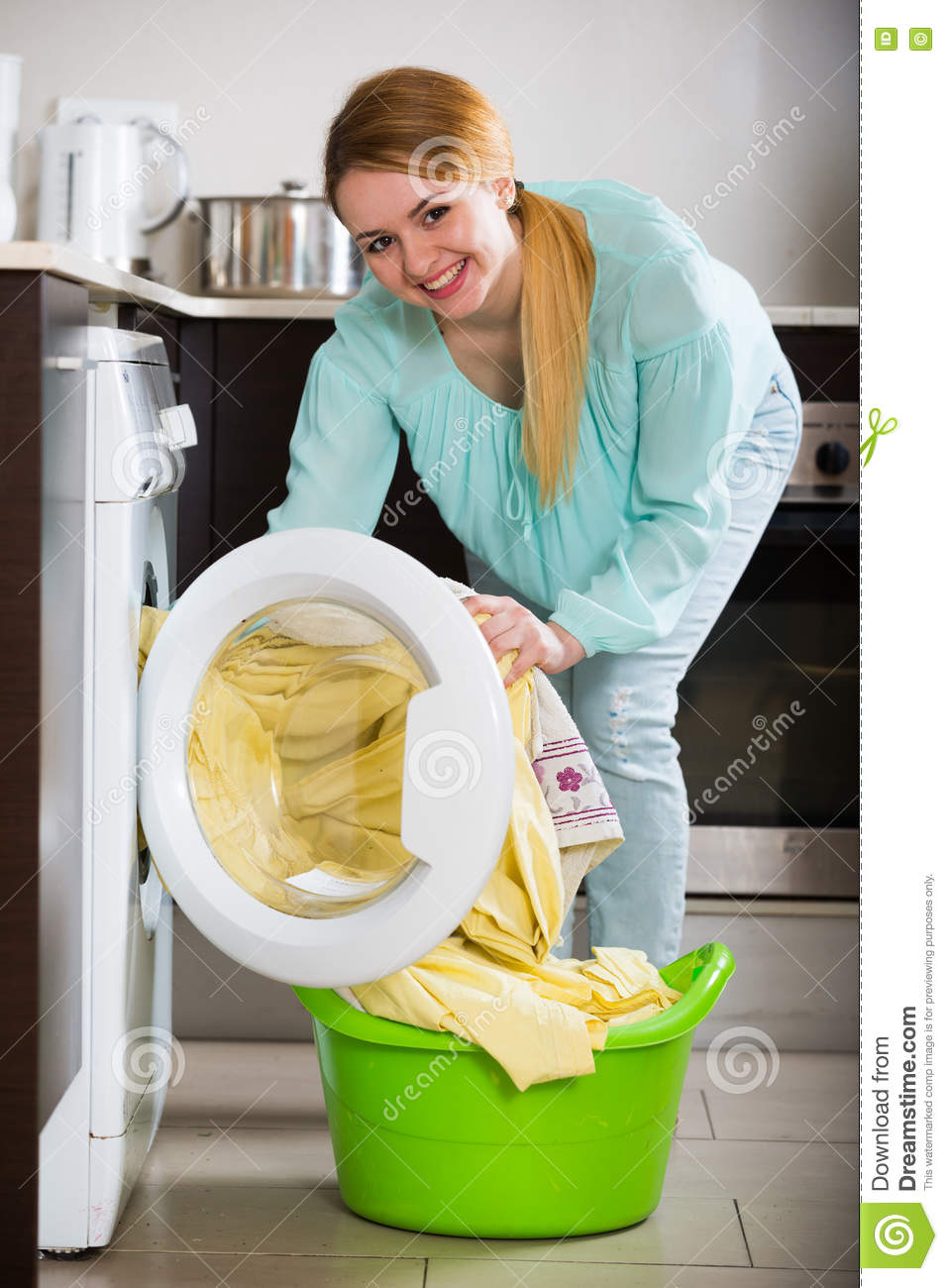 Happy Young Woman Doing Laundry In Kitchen And Smiling Stock Photo ...