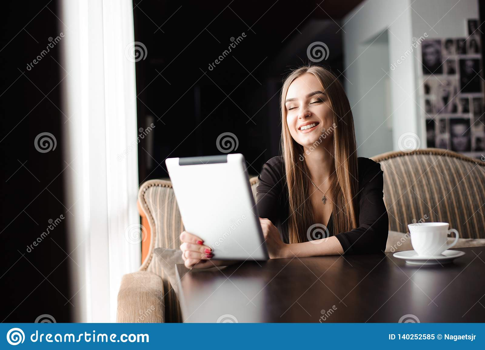 Happy young woman drinking coffee, tea and using tablet computer in a coffee shop