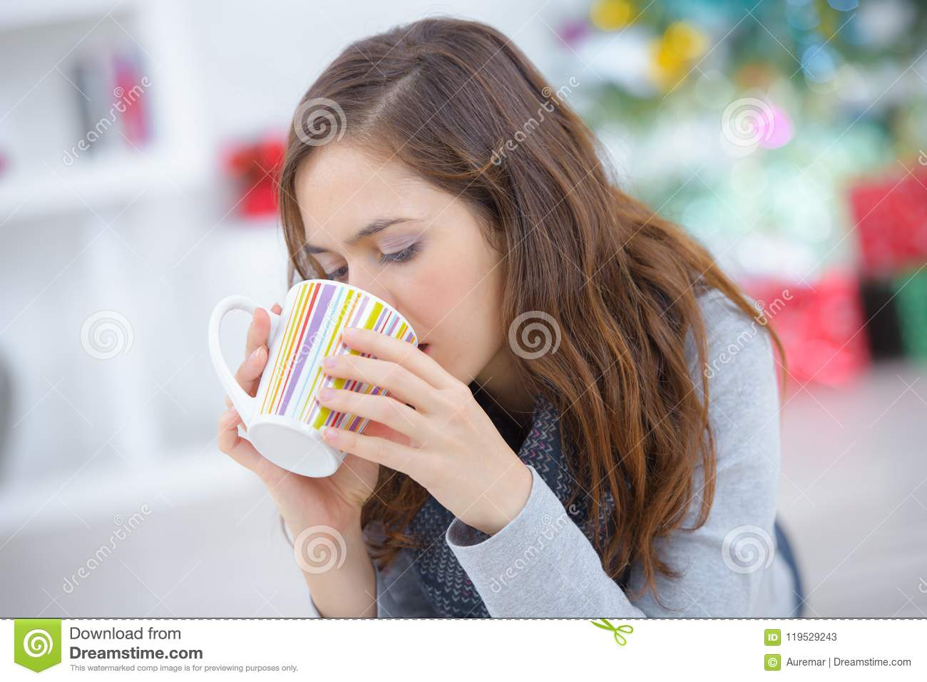 Happy young woman drinking tea at home while relaxing