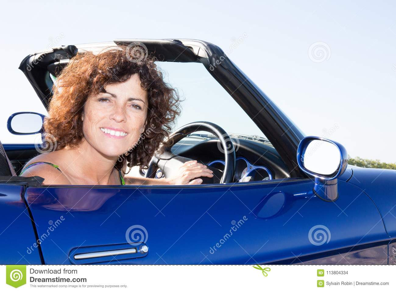 happy young woman driving her convertible top automobile on bright sunny day