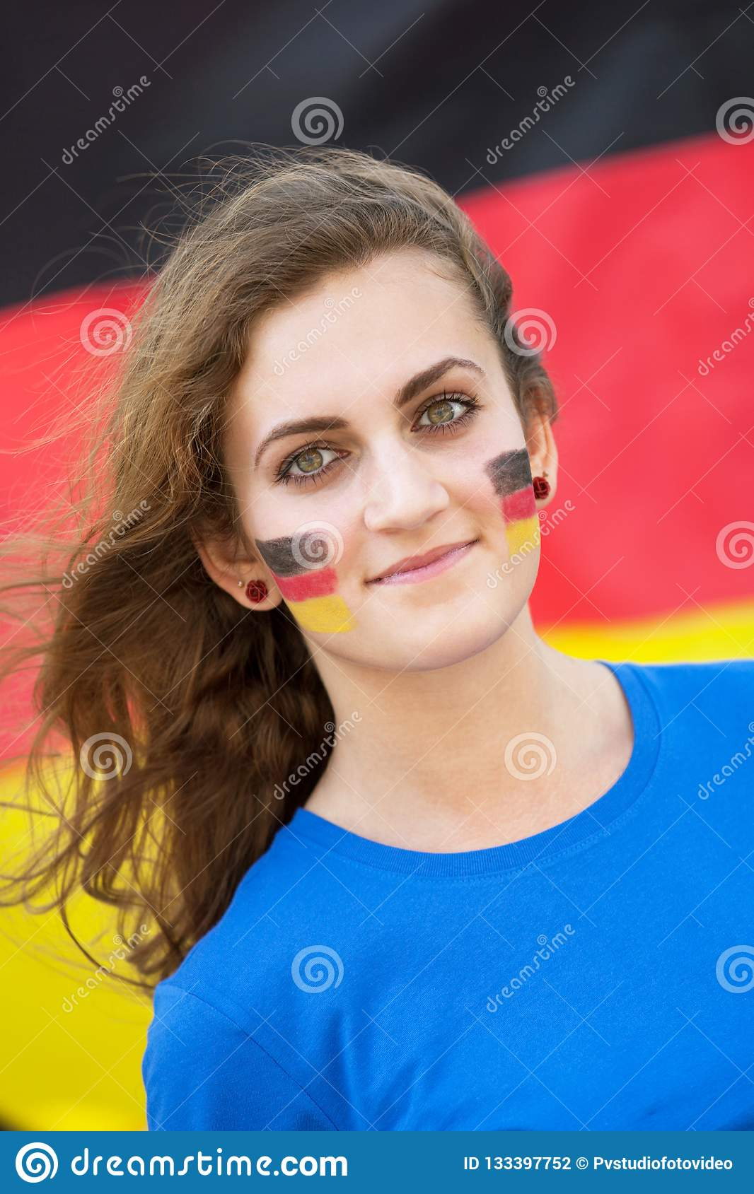 Happy young woman with German flag on cheeks on the background