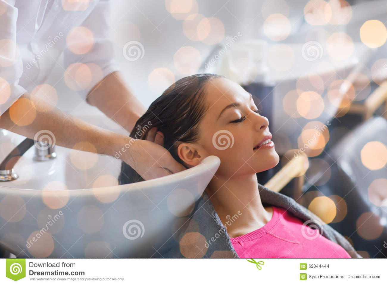 Young woman with hairdresser washing head at hair salon for Salon younga