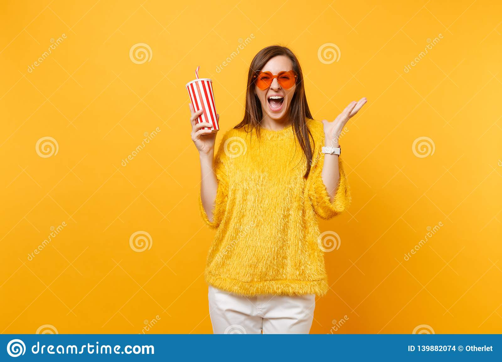 Happy young woman in heart orange glasses spreading hands, screaming, holding plastic cup with cola or soda isolated on