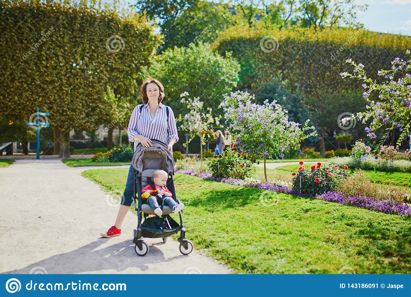 Happy young woman with her little baby girl in stroller