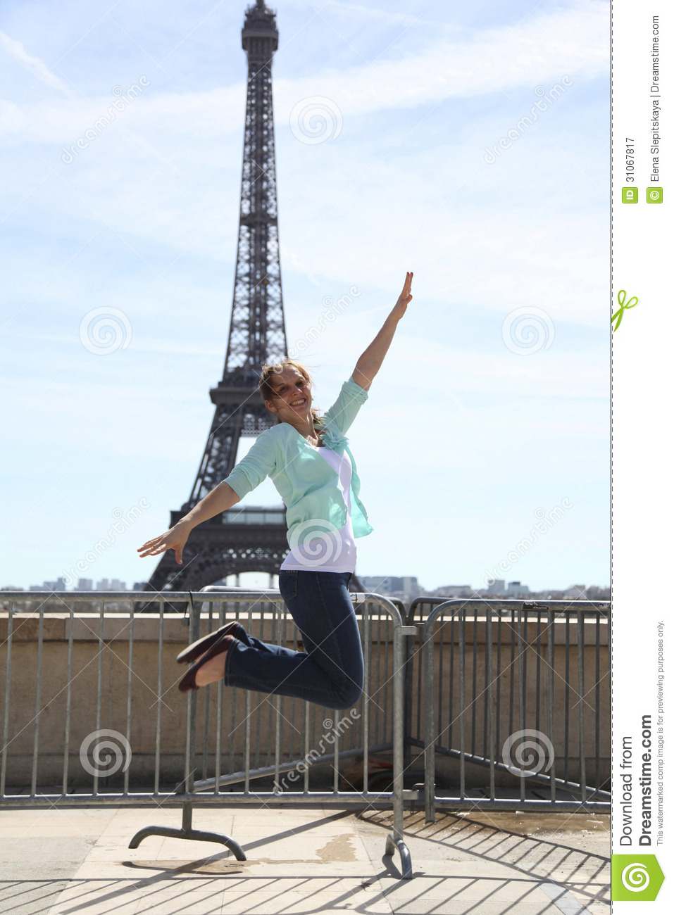 Happy young woman jumping against eiffel tower royalty free stock