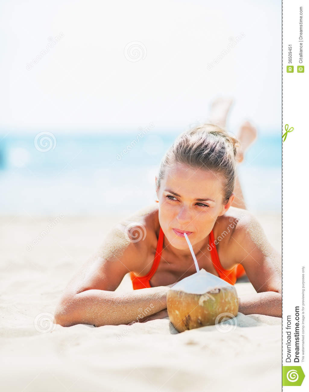 Happy young woman laying on beach and drinking coconut milk