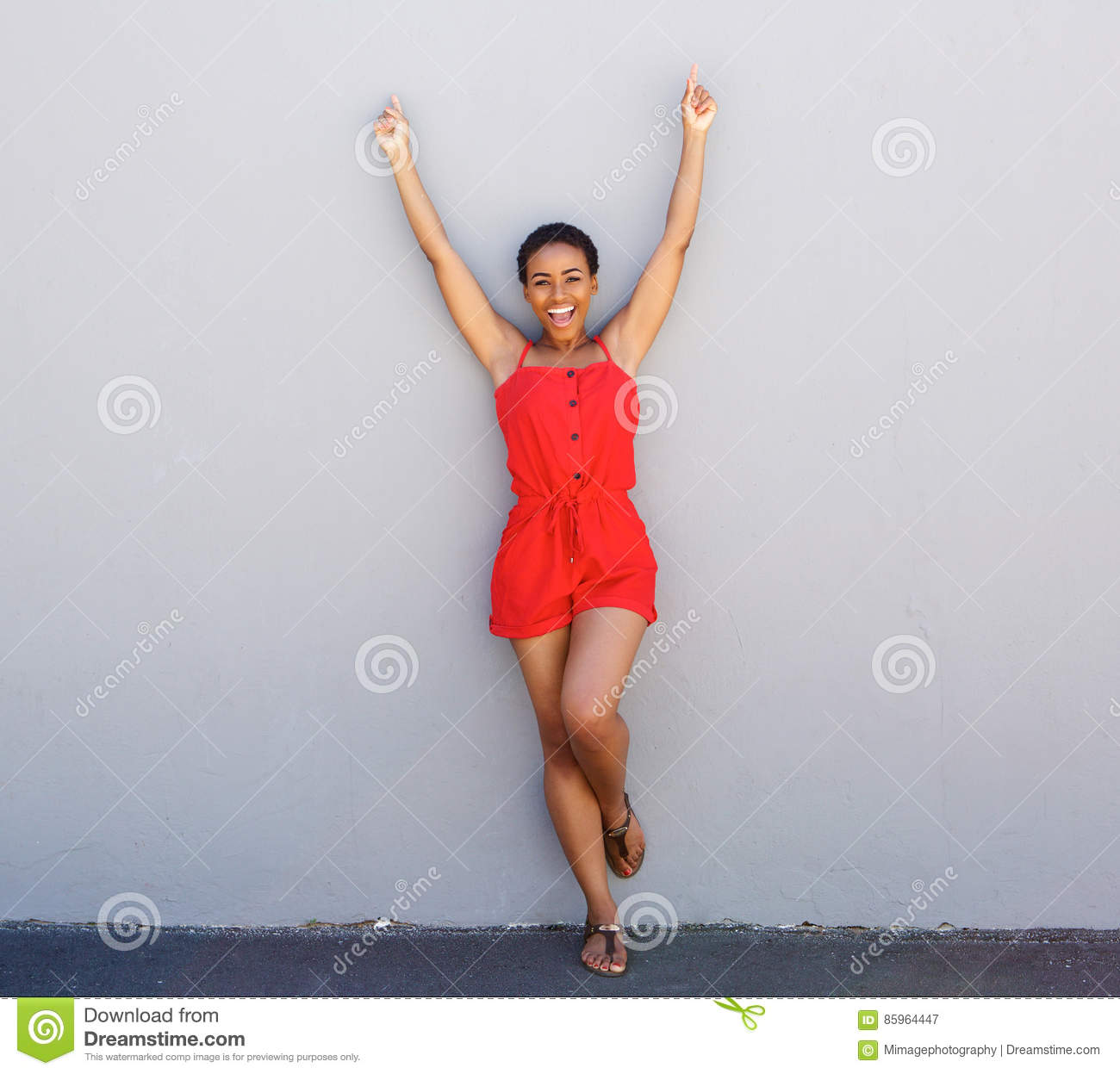 Happy young woman leaning against gray wall with arms raised