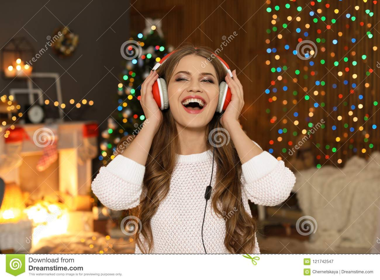 Happy young woman listening to Christmas music