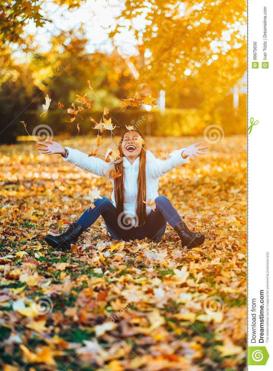 Happy young woman in park on sunny autumn day, laughing, playing leaves. Cheerful beautiful girl in white sweater during autumn se