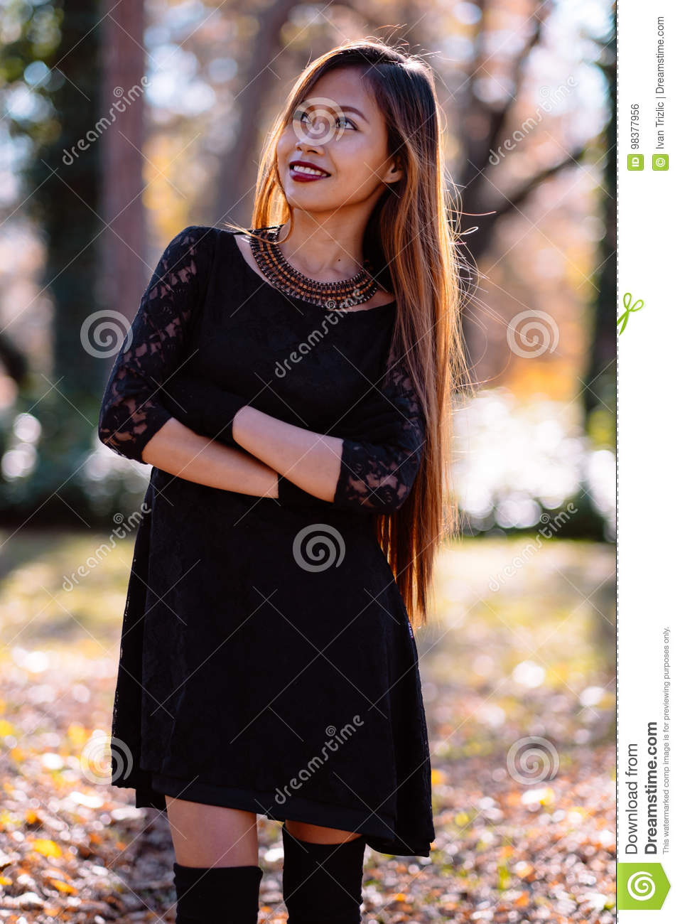 Happy young woman in park on sunny autumn day, smiling. Cheerful beautiful girl in black retro dress autumn fashion style