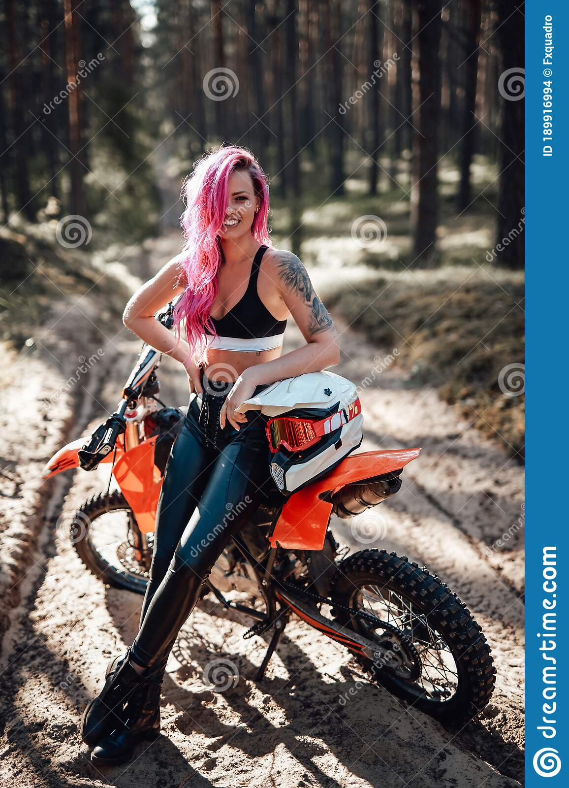 Smiling Young Woman With Pink Hair And Tattoo On Hand Sitting On Her Modern Motocross Bike In Woods Stock Photo Image Of Enjoying Helmet 189916994