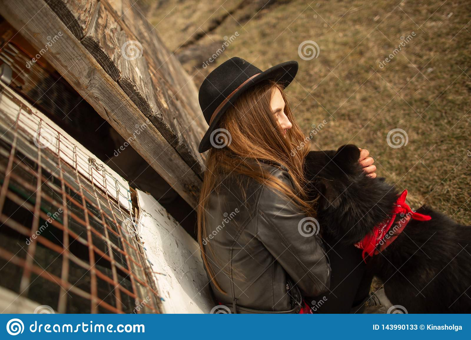 Happy young woman plaing with her black dog Brovko Vivchar in fron of old wooden house