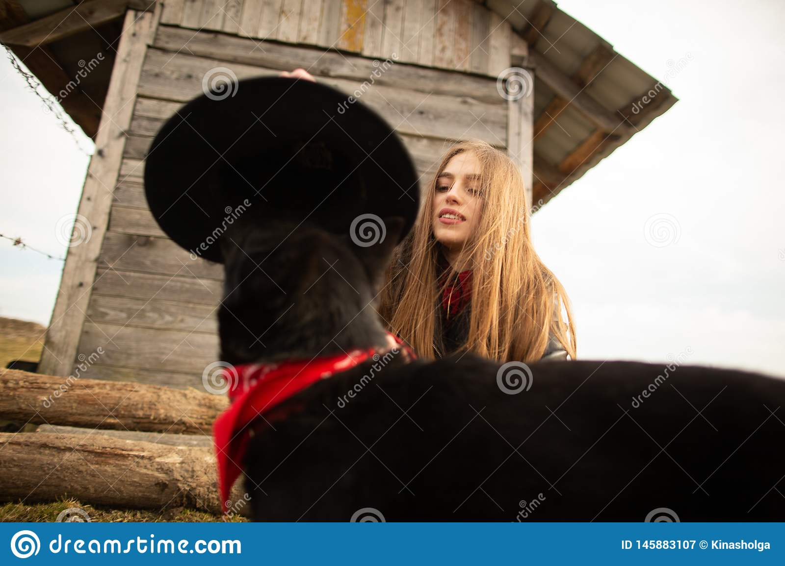 Happy young woman plaing with her black dog in fron of old wooden house. Girl tries a hat to her dog