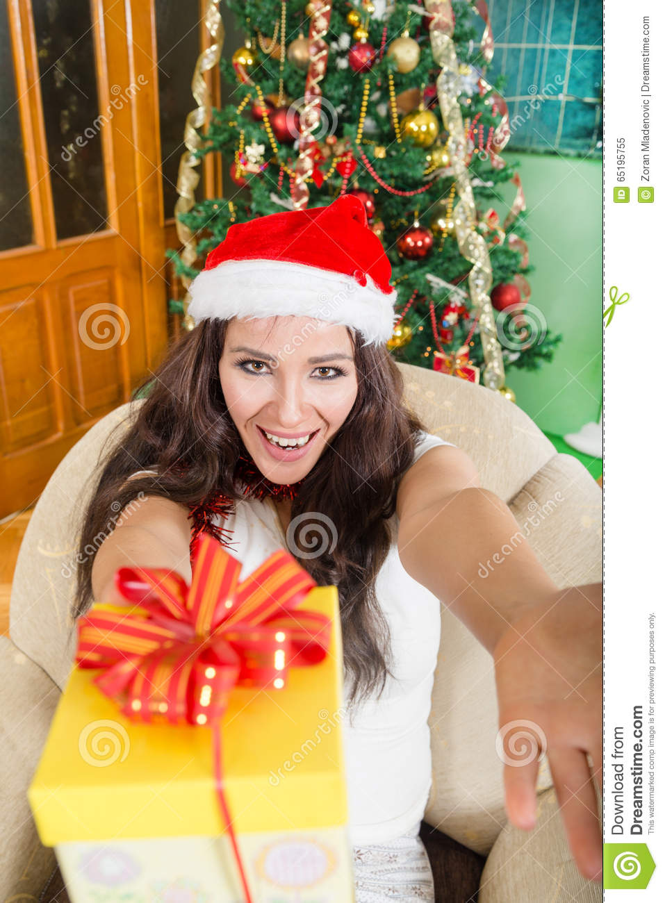 Happy young woman proffering gift box with joy and generosity