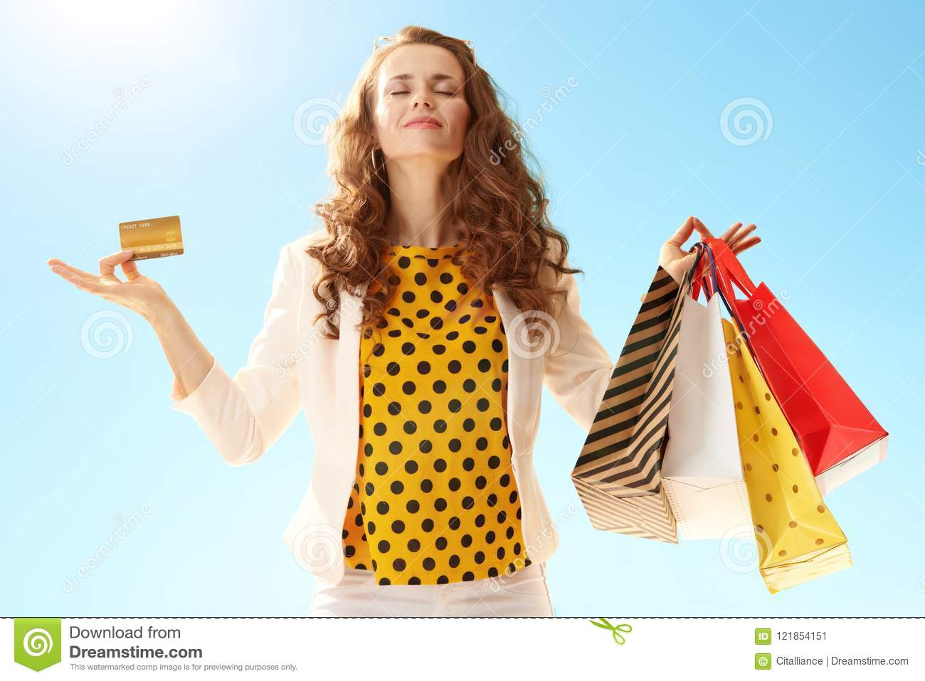 Happy young woman with shopping bags and credit card doing yoga
