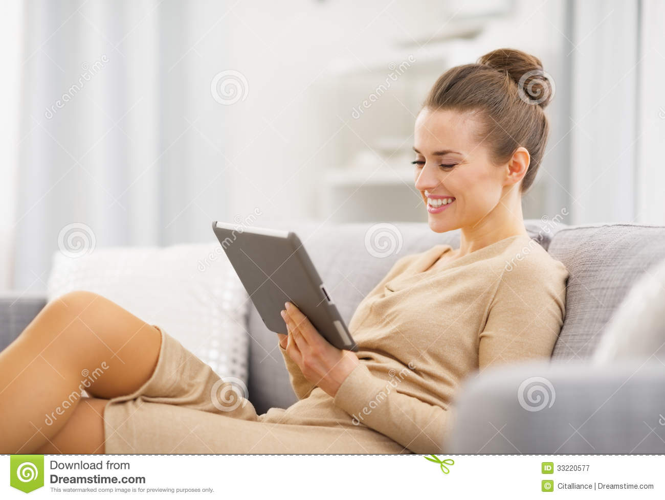 Happy young woman sitting on couch and working on tablet pc