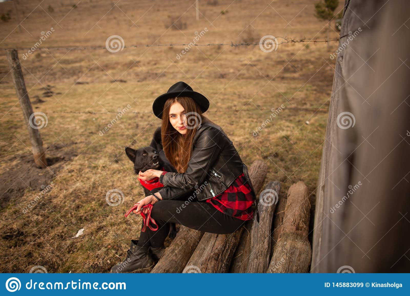 Happy young woman sitting with her black dog in fron of old wooden house