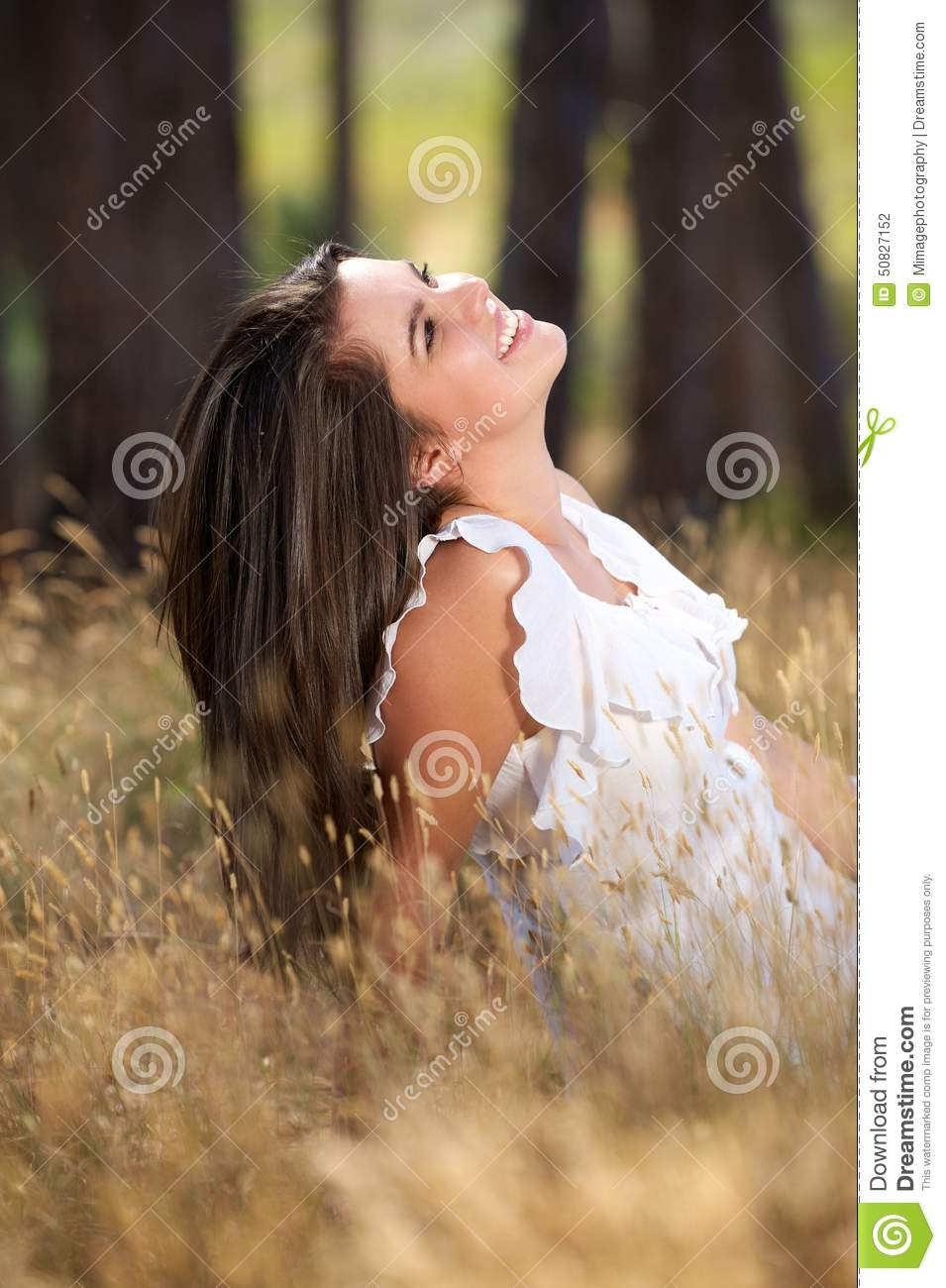 Happy young woman sitting in meadow and smiling