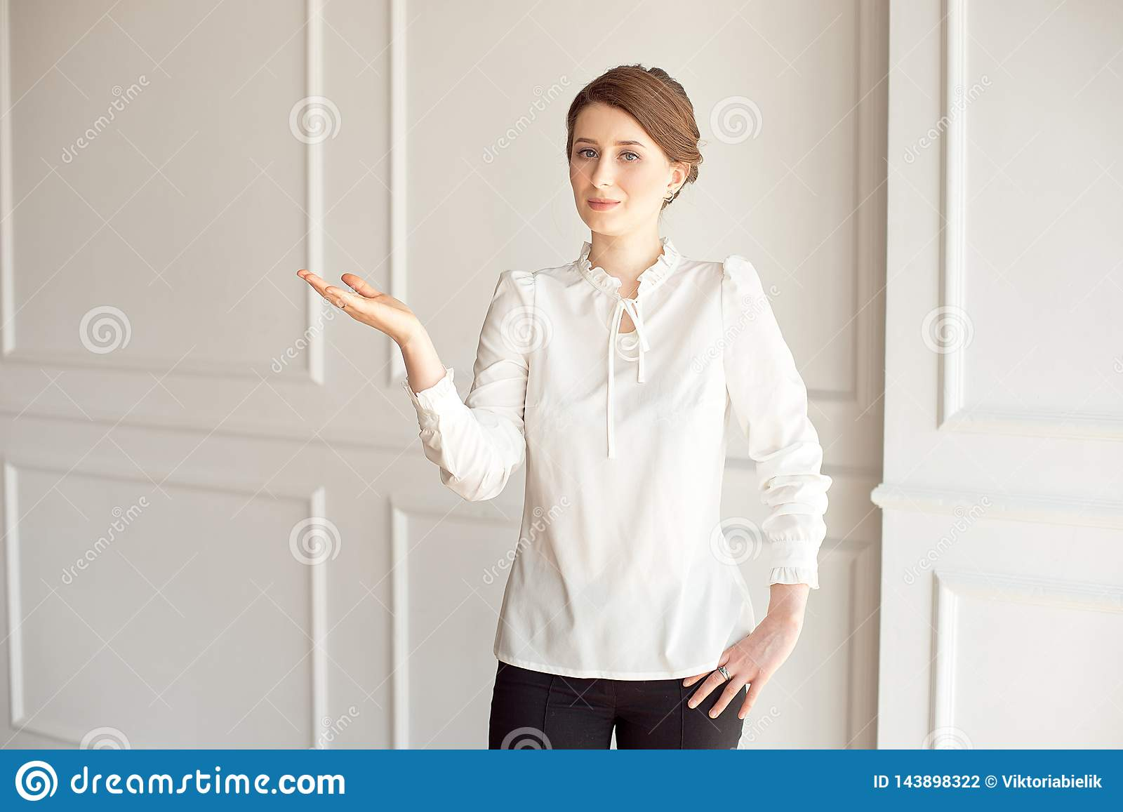 Happy young woman standing near a white wall. Hand showing a place for pointing copyspace