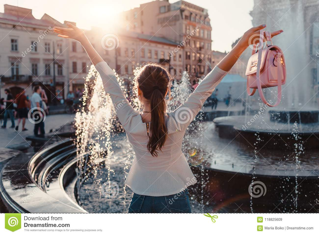 Happy young woman tourist looks at fountain. Summer travel. Vacation and holidays concept