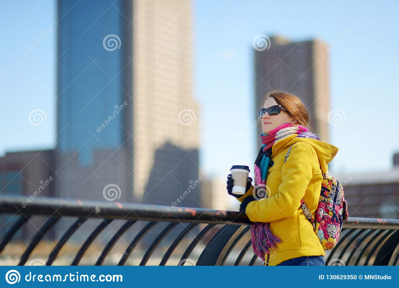 Happy young woman tourist sightseeing in New York City at sunny spring day. Female traveler drinking coffee in downtown Manhattan.