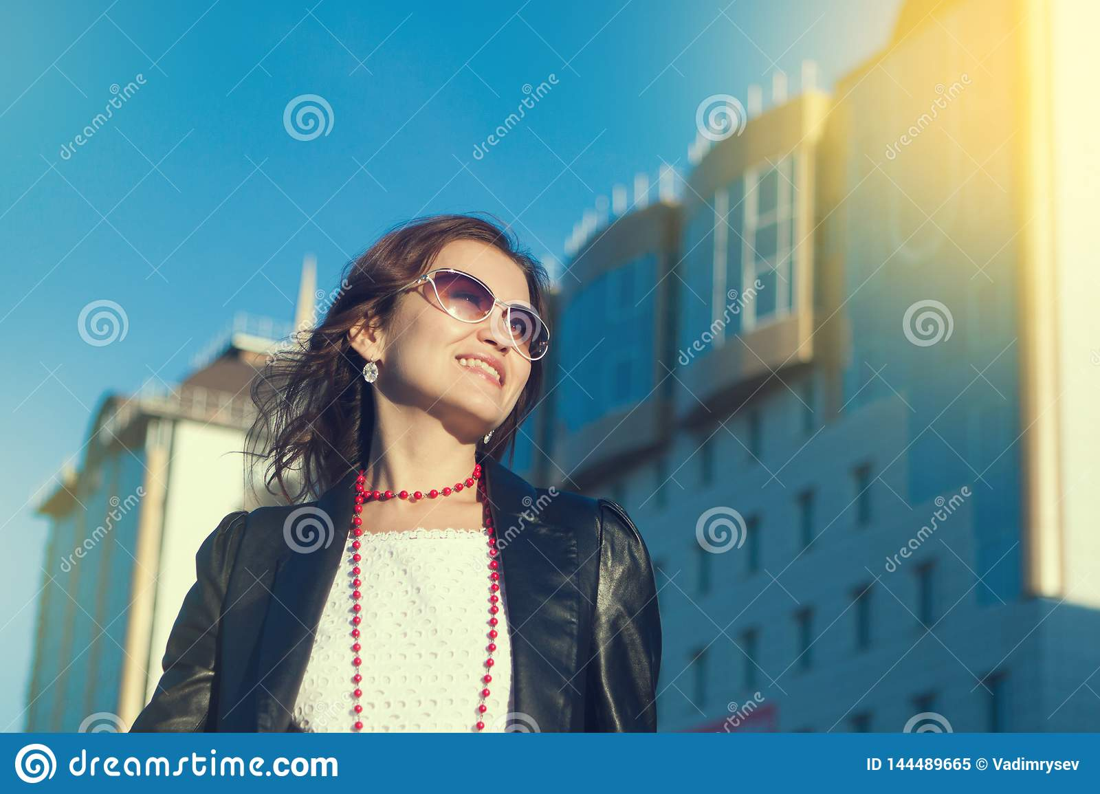 Happy young woman walking on a city street.