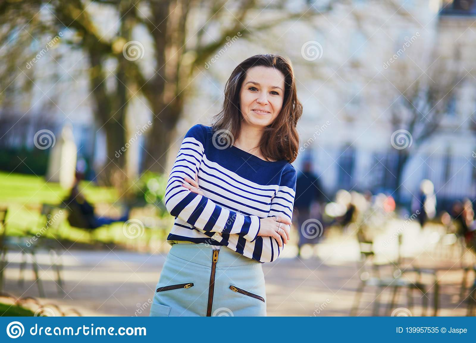 Happy young woman walking in the Luxembourg garden of Paris