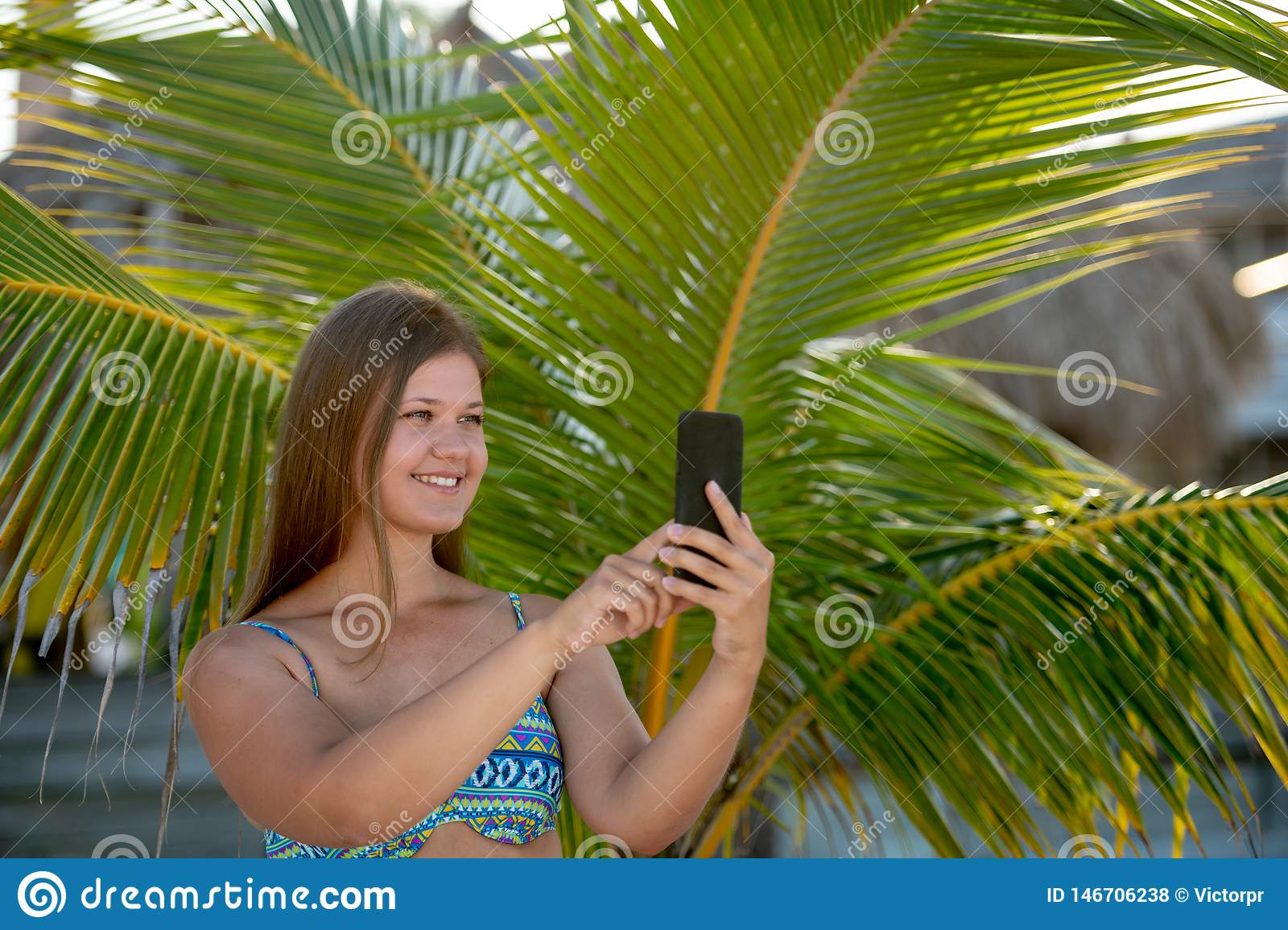 Happy young woman makes selfie on the beach