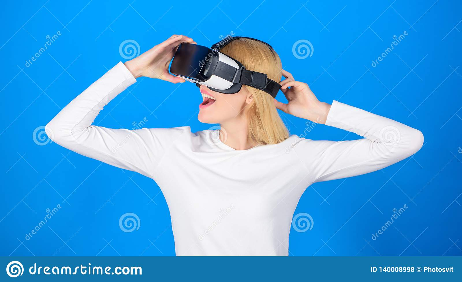 Happy young woman wearing virtual reality goggles watching movies or playing video games. Person with virtual reality