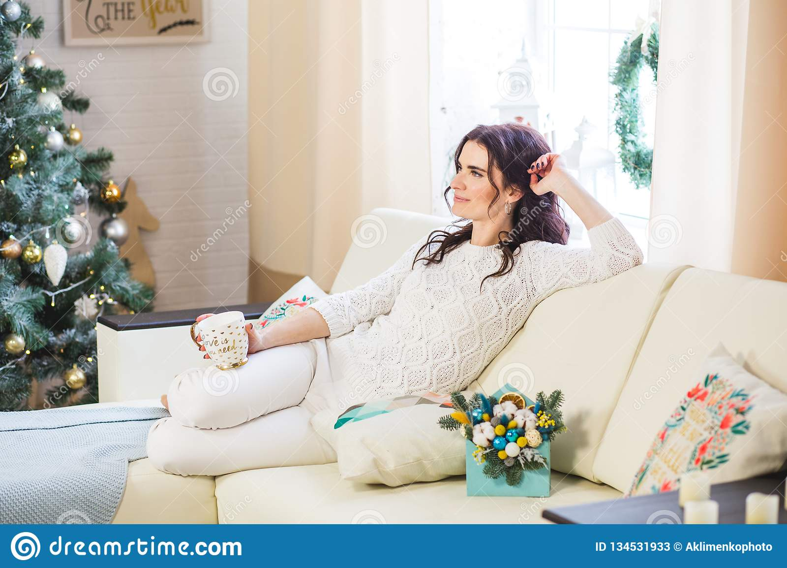Happy young woman in white knitted wearing with cup of coffee or tea at home