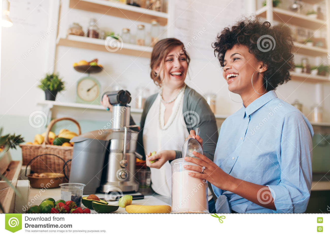 Happy young women working at juice bar counter