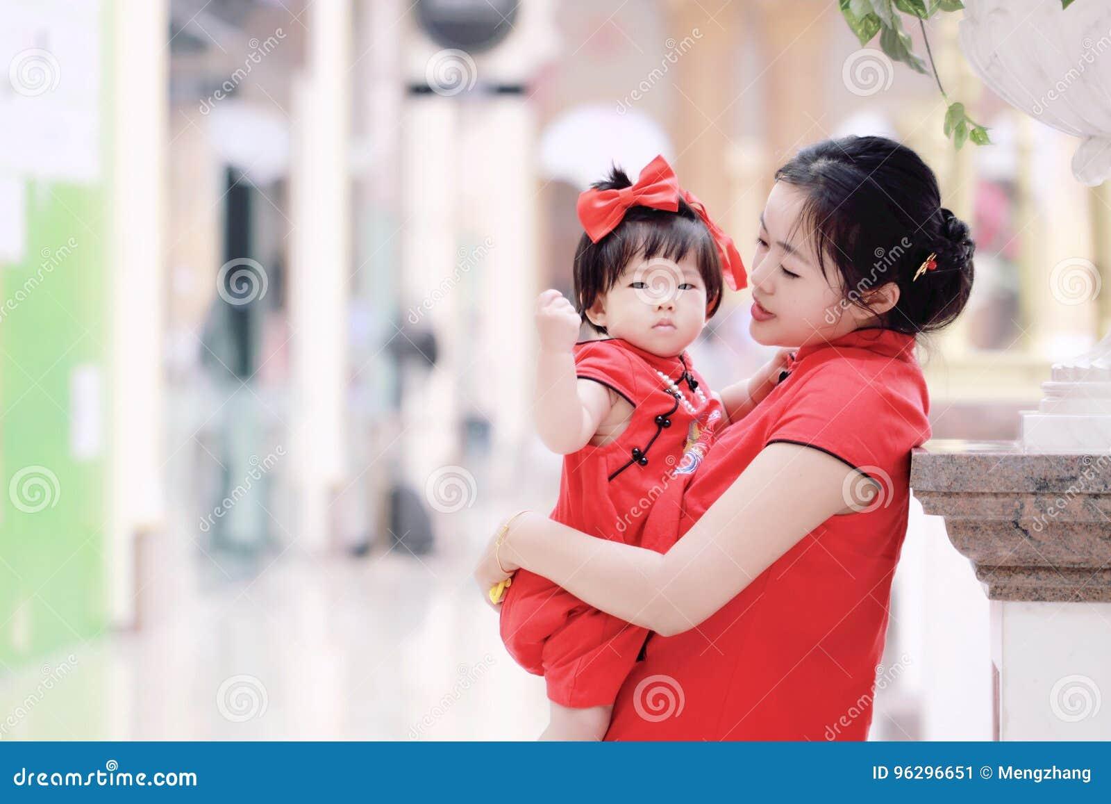 Har den unga kinesiska modern för den lyckliga familjen gyckel med att behandla som ett barn i Kina traditionell cheongsam