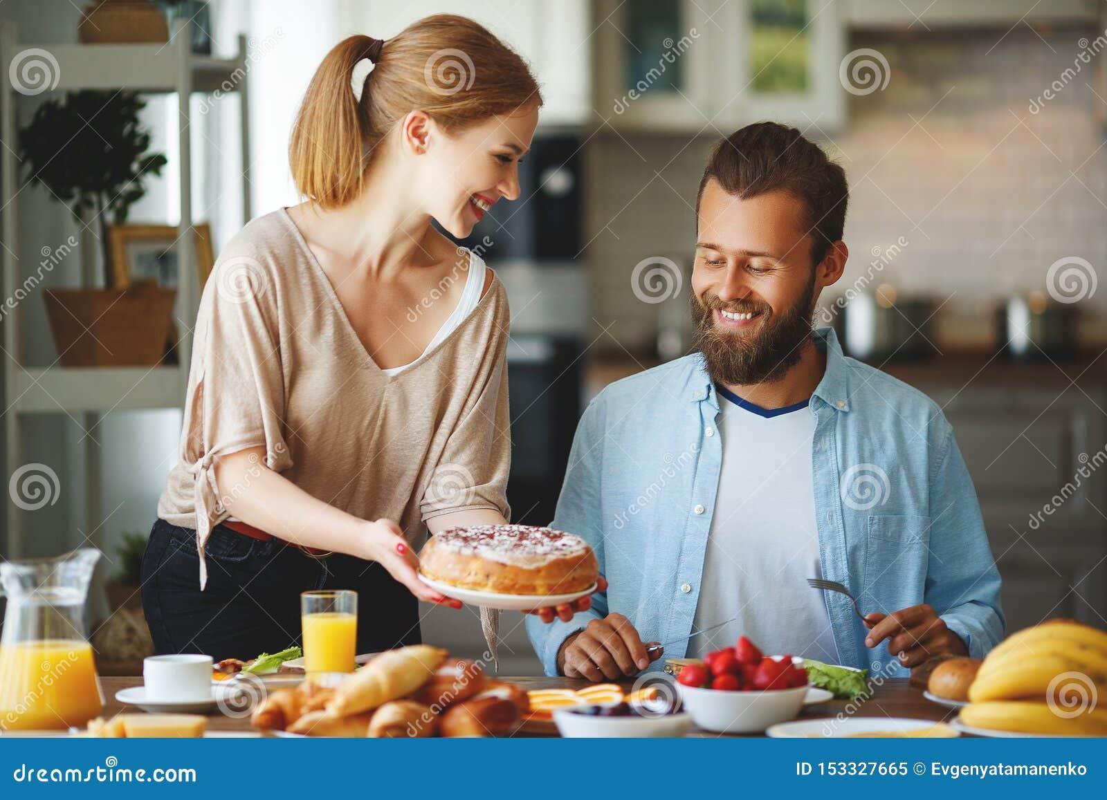 Har lyckliga par för familj frukosten i kök i morgon