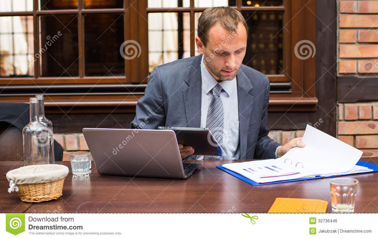 Hard Working Businessman In Restaurant With Laptop And Pad ...