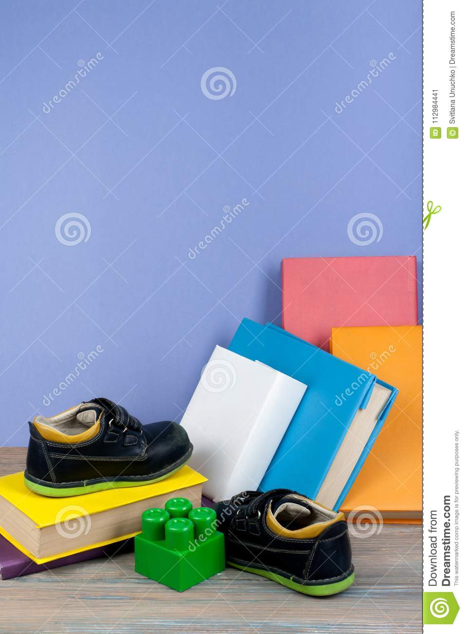 Hardback colorful books, toy, shoes on wooden table. Back to school. Copy space for text. Education business concept.